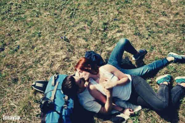 couple lying on grass bag kissing