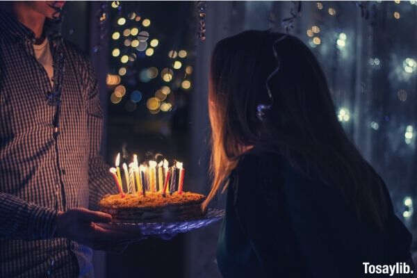 woman making a wish blowing candles