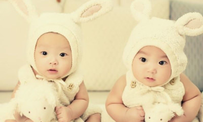 two-babies-wearing-white-headdress-white-holding-white-plush-toys