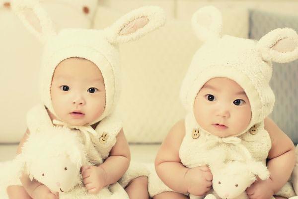 two-babies-wearing-white-headdress-white-holding-white-plush-toys