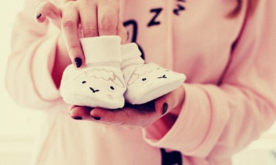 woman-holding-baby-s-pair-of-white-shoes