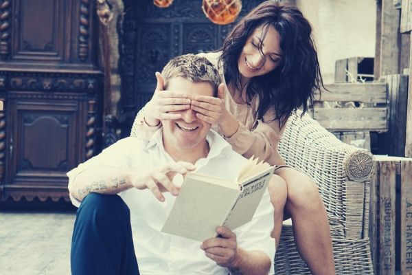 feature-woman-sitting-sofa-covering-mans-eyes-holding-book