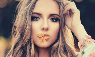 feature-woman-with-orange-petaled-flower-on-her-lips