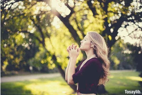 woman in maroon dress praying in a park