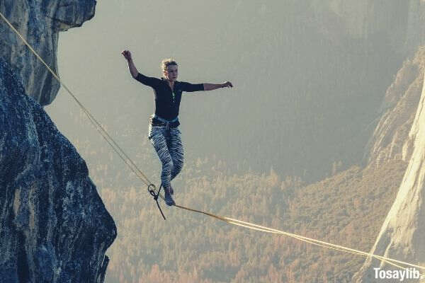 Photo of brave woman walking on tightrope