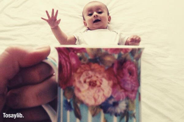 baby lying white bed cup flower design