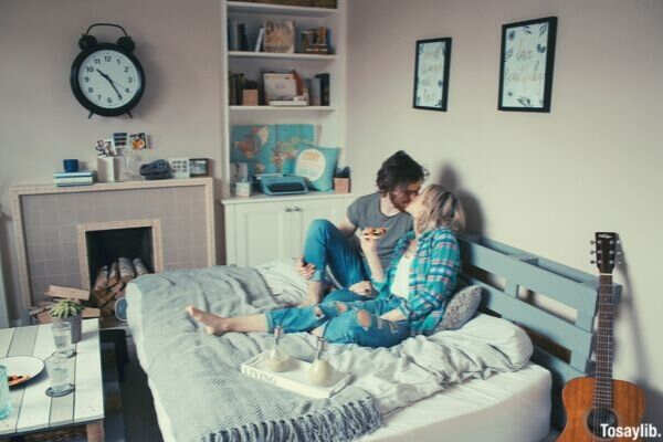couple bed sitting kissing happy guitar clock