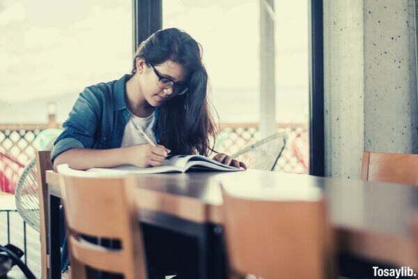 girl studying glasses writing pen table