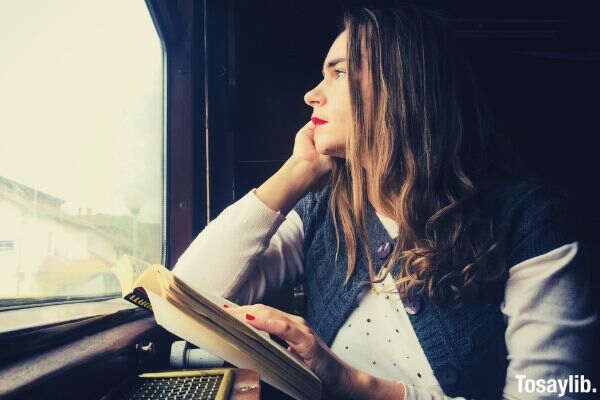 woman in train sitting next to the window and looking outside with a book in her hand