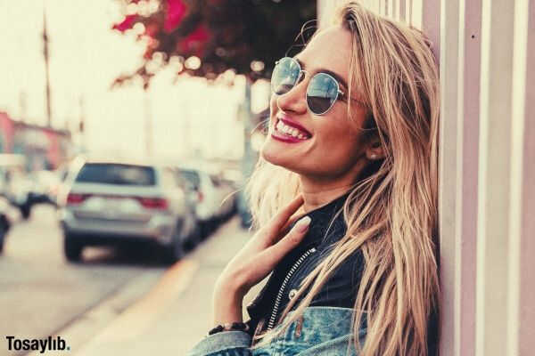 woman leaning on wall standing smiling sunglasses denim jacket street car