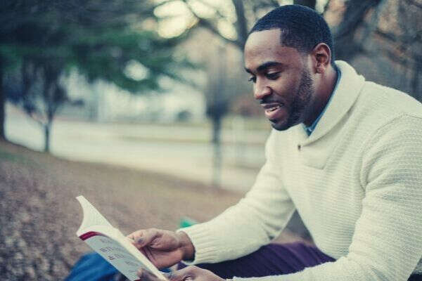 black-american-smiling-long-sleeves-reading-book