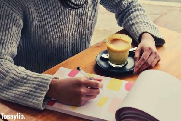 woman holding coffee saucer writing