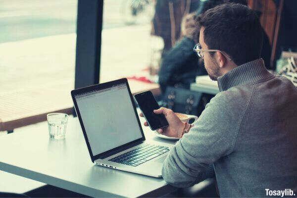 man laptop smartphone sweater