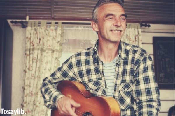 men playing guitar smile father happy senior mature adult grandpa funny face baby boomer