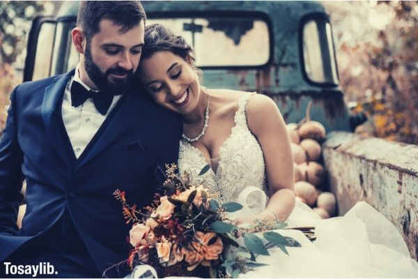 wedding couple sitting at back of truck