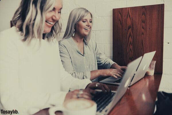 feature two women colleagues laptop