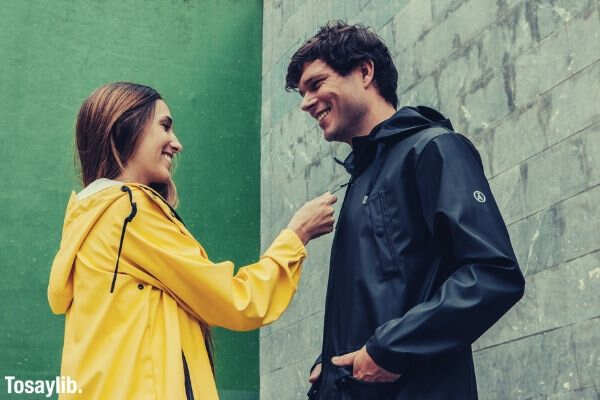couple smiling at each other yellow black jacket wall green