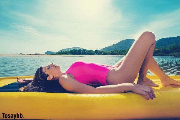 woman pink swim suit sun bathing lake
