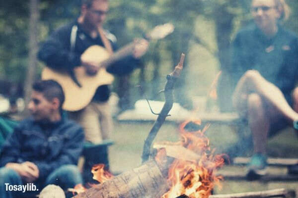 people camping bonfire playing guitar