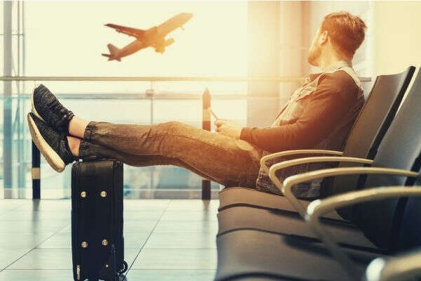 man-sitting-travel-plane-luggage-bag