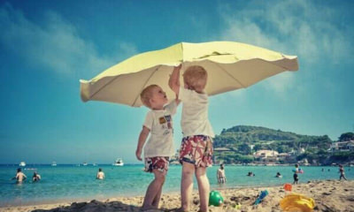 feature-two-kids-playing-under-the-umbrella-sand