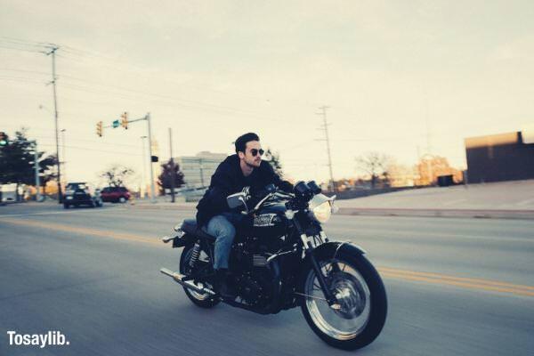 guy driving motorcyle wearing black jacket street vehicles