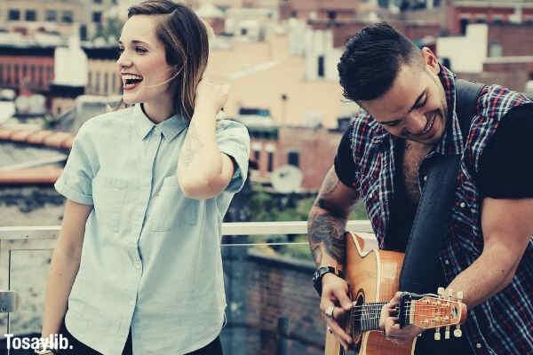 woman smiling man playing guitar buildings