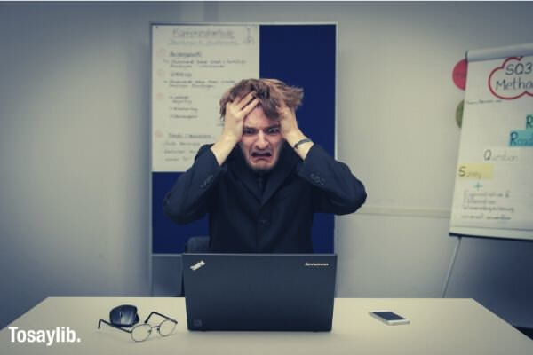 guy exhausted office laptop