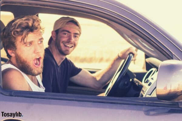 two guys smiling riding a pickup driving