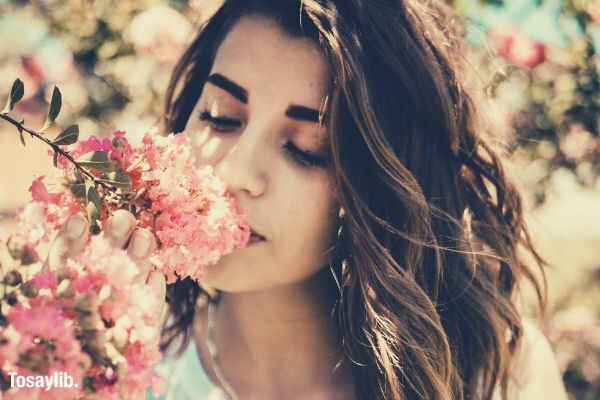woman smelling pink flower