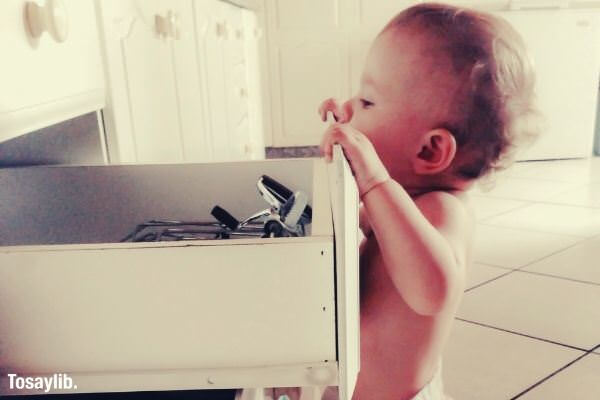 curious baby opening drawer