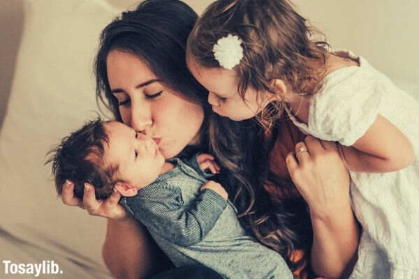 mom kissing baby with sister