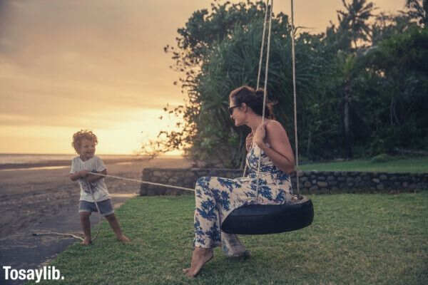 mom swinging pulled by son beach side