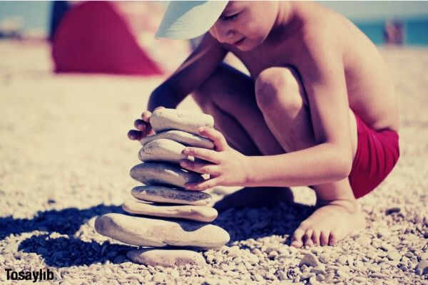01 boy building stones on beach