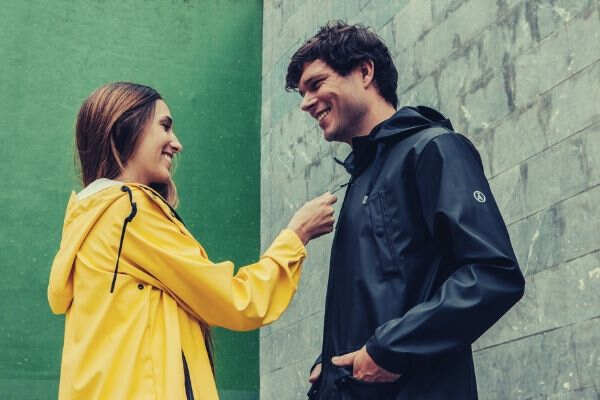 couple-teasing-at-each-other-yellow-black-jacket-wall-green