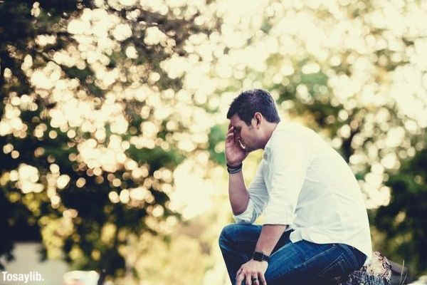 man praying close eyes sitting on a broken tree trunk
