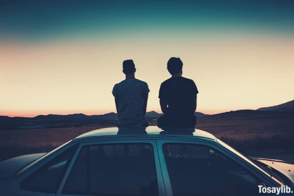 two men friends sitting on the car roof