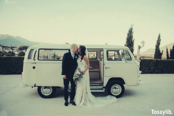 newly wed couple kiss vehicle
