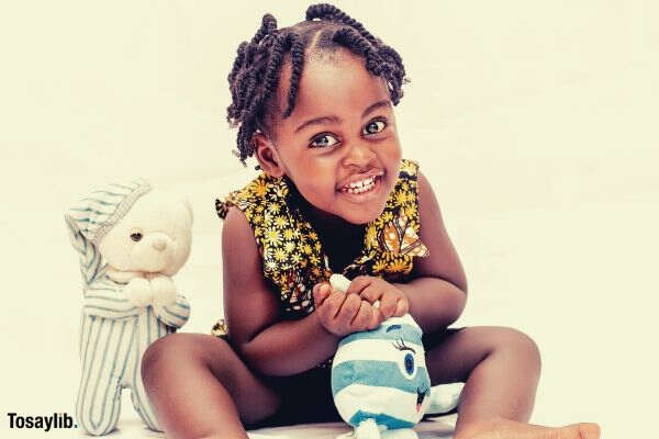 toddler girl smiling and touching toy black american