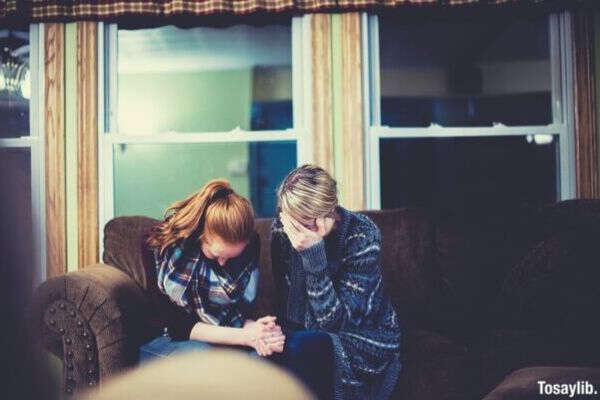 two woman praying while sitting on the couch