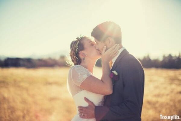 woman wearing a wedding dress kisses a man wearing a gray suit in the middle of a field in front