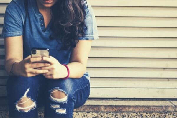 woman-sitting-by-the-corner-texting-smartphone