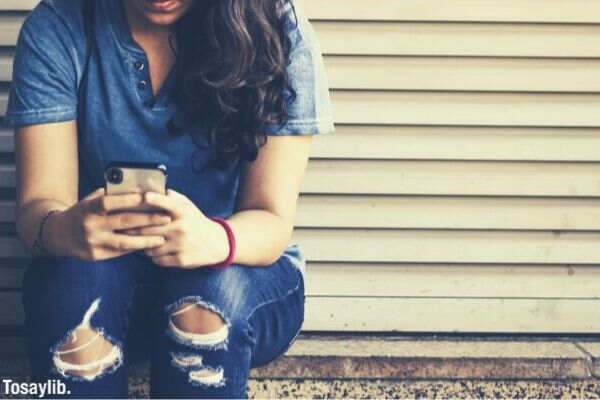 woman sitting by the corner using smartphone