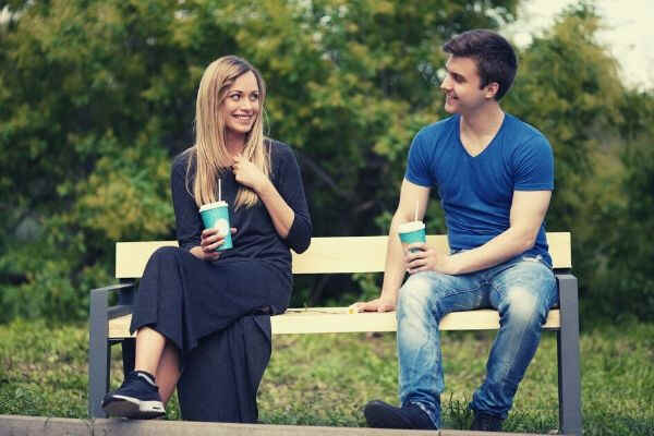 sitting-on-a-bench-and-drinking-a-couple-talking
