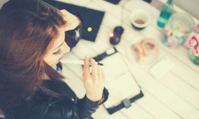 young-woman-thinking-with-pen-while-working-studying-at-her-desk