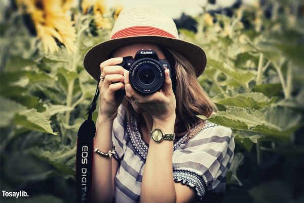 selective focus photography of woman holding dslr camera sunflower plant
