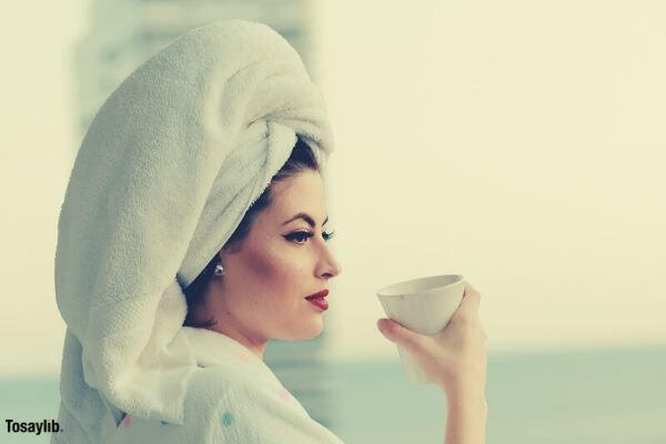 photo of woman wearing bathrobe holding mug