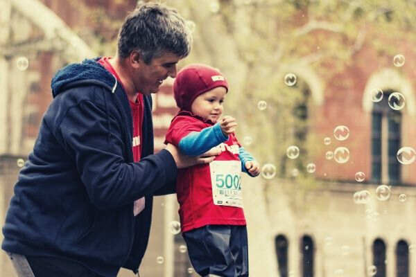 man-carrying-baby-playting-bubbles-jackets-outdoor