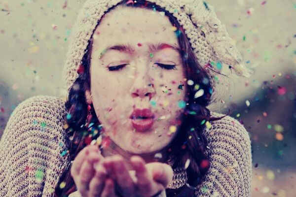 teen-girl-blowing-colorful-glitters