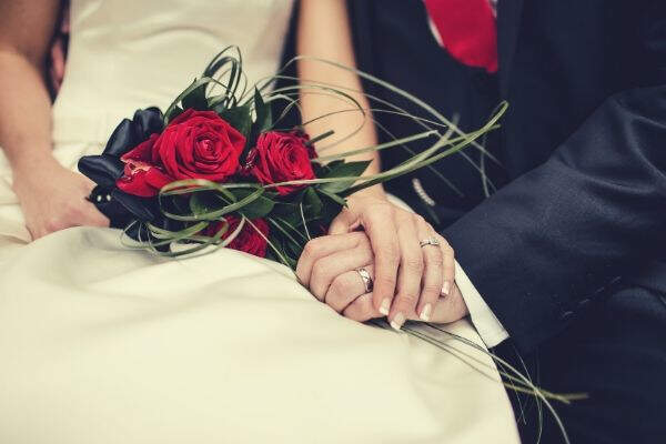 wedding-couple-holding-hands-bouquet-roses